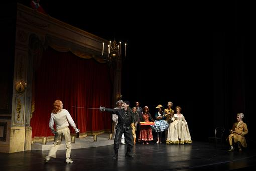 jetzt hat der Umzug (und Perückenwechsel) auf den Punkt geklappt: Marquise und Marquis, Blumenmädchen und Pagen sind an ihrem Platz und beobachten den ersten Fechtkampf von Cyrano de Bergerac